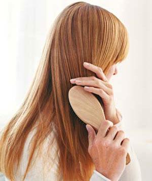 femme rousse qui brosse ses cheveux