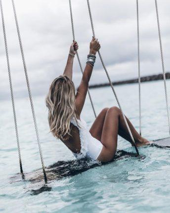 Femme blonde sur une balançoire en mer. Blonde girl in the sea