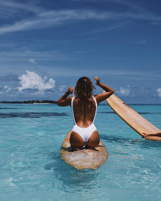 femme cheveux mouillé effet wavy sur place de surf. Women with salty hair on a surf board